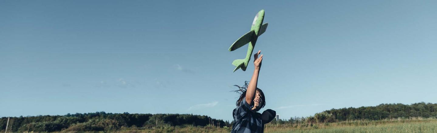 Boy flying a toy plane in a field